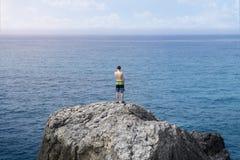 Hombre joven que se coloca en un acantilado Imagen de archivo