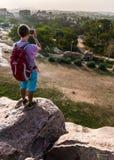 Hombre joven que se coloca en una montaña y que hace la foto del valle Foto de archivo libre de regalías