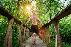 Hombre joven que se coloca en una pasarela en el bosque imagenes de archivo