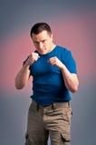 hombre joven que se coloca en una posición del boxeo Fotos de archivo libres de regalías