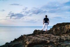 Hombre joven que se coloca en una roca Foto de archivo