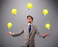 Hombre joven que se coloca y que hace juegos malabares con las bombillas Imagen de archivo