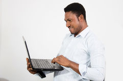 Hombre joven que se coloca y que trabaja con su ordenador portátil Imágenes de archivo libres de regalías