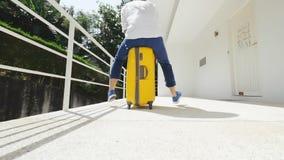 Hombre joven que se divierte al aire libre que monta una maleta amarilla almacen de metraje de vídeo
