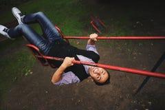 Hombre joven que se divierte en el oscilación en el patio Imagen de archivo libre de regalías