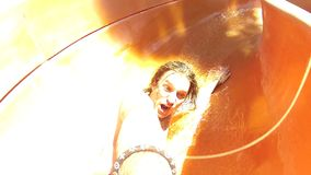 Hombre joven que se divierte que monta abajo del tubo en un parque del agua almacen de metraje de vídeo