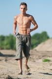 Hombre joven que se ejecuta en la playa Foto de archivo libre de regalías