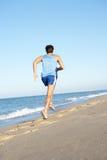 Hombre joven que se ejecuta a lo largo de la playa Fotos de archivo libres de regalías