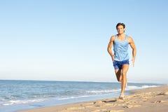 Hombre joven que se ejecuta a lo largo de la playa Fotos de archivo