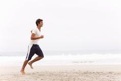 Hombre joven que se ejecuta a lo largo de la playa del invierno Fotos de archivo libres de regalías