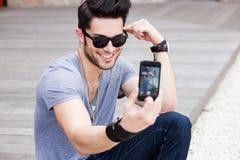 Hombre joven que se fotografía con un smartphone Fotos de archivo