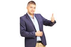 Hombre joven que se inclina contra una pared y que da un pulgar para arriba Fotos de archivo libres de regalías
