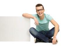 Hombre joven que se inclina en tarjeta en blanco Imagenes de archivo