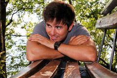 Hombre joven que se inclina en un banco en el parque Imagen de archivo