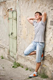 Hombre joven que se inclina en una pared del grunge Fotos de archivo libres de regalías