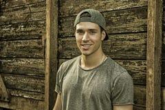 Hombre joven que se opone a la pared de madera de los tablones Imagen de archivo