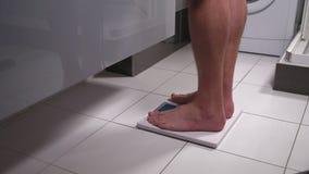 Hombre joven que se pesa en el cuarto de baño almacen de video
