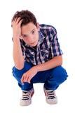 Hombre joven que se pone en cuclillas, preocupado Imagenes de archivo
