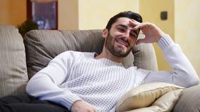 Hombre joven que se ríe de la show televisivo divertida almacen de video