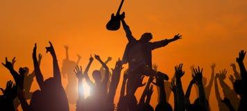 Hombre joven que se realiza con una guitarra delante de la muchedumbre Imagenes de archivo