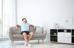 Hombre joven que se relaja debajo del acondicionador de aire foto de archivo libre de regalías