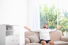 Hombre joven que se relaja debajo del acondicionador de aire imágenes de archivo libres de regalías