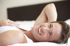 Hombre joven que se relaja en cama Fotografía de archivo