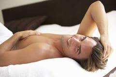 Hombre joven que se relaja en cama Foto de archivo libre de regalías