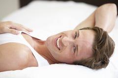 Hombre joven que se relaja en cama Foto de archivo