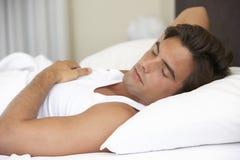 Hombre joven que se relaja en cama Imagen de archivo