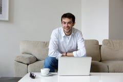 Hombre joven que se relaja en casa con el ordenador portátil Imágenes de archivo libres de regalías