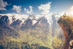 Hombre joven que se relaja en el acantilado de la montaña al aire libre Fotos de archivo libres de regalías