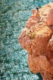 Hombre joven que se relaja en el acantilado rocoso con el mar azul en fondo Fotografía de archivo