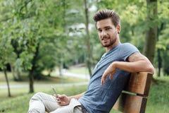 Hombre joven que se relaja en el parque Fotos de archivo libres de regalías
