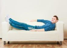 Hombre joven que se relaja en el sofá Fotos de archivo libres de regalías