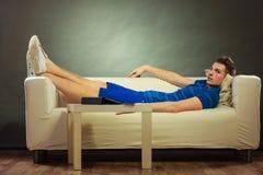 Hombre joven que se relaja en el sofá Imágenes de archivo libres de regalías