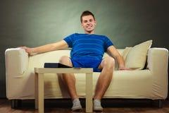 Hombre joven que se relaja en el sofá Imagen de archivo libre de regalías