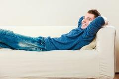 Hombre joven que se relaja en el sofá Fotografía de archivo libre de regalías