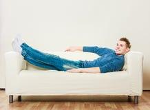 Hombre joven que se relaja en el sofá Imagenes de archivo