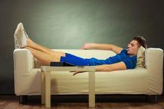 Hombre joven que se relaja en el sofá Imagen de archivo