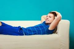 Hombre joven que se relaja en el sofá en azul Fotografía de archivo
