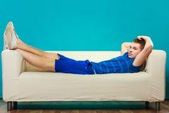 Hombre joven que se relaja en el sofá en azul Fotos de archivo