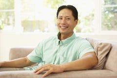 Hombre joven que se relaja en el sofá en el país imagen de archivo libre de regalías