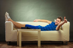 Hombre joven que se relaja en el sofá que hace el pulgar para arriba Imagenes de archivo