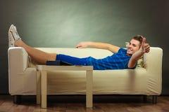 Hombre joven que se relaja en el sofá que hace el pulgar para arriba Imagen de archivo