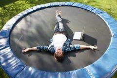 Hombre joven que se relaja en el trampolín con la computadora portátil Fotos de archivo