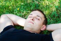 Hombre joven que se relaja en la hierba Fotografía de archivo