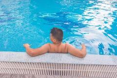 Hombre joven que se relaja en la piscina Imagen de archivo