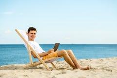 Hombre joven que se relaja en la playa Imagen de archivo