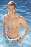 Hombre joven que se relaja en piscina imagenes de archivo